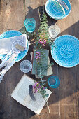 Wooden table set with blue plates in sunshine