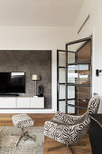 Easy chair with matching footstool in elegant living room with open glass door and TV on floating cabinet