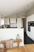 Wooden bench against counter in white fitted kitchen