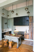 Stools in front of old workbench used as island counter in rustic kitchen