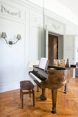 Grand piano in historical interior with panelled walls and parquet floor