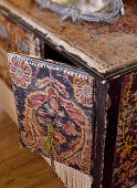 Detail of black cabinet covered with pieces of old carpet