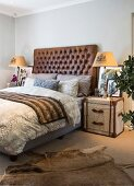 Bed with leather headboard, steamer trunk used as bedside table and animal-skin rug in bedroom