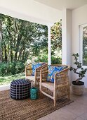 Blue patterned scatter cushions on two wicker armchairs on roofed terrace