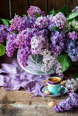 Cup of coffee in front of bouquet of purple lilac