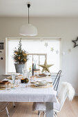 Table festively set in white in front of small Christmas tree on window sill