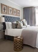 Double bed with button-tufted headboard and gilt side table in bedroom