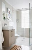 Shower area with glass screen in simple bathroom