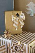 Weihnachtsgeschenke dekorativ verpackt in goldfarbenem Papier mit handgemachter Schleife
