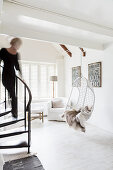 Woman walking down winding staircase into white living room with hanging chair