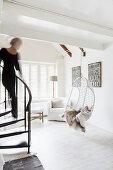 Frau auf Wendeltreppe zum weißen Wohnzimmer mit Hängesessel