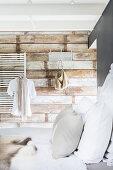 Blick vom Bett auf eine Wand mit Fototapete in Holzoptik