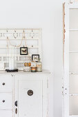 Apothecary jars and rows of hooks on shabby-chic dresser