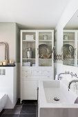 Old glass-fronted cabinet and twin sinks in white bathroom