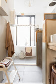 Small compartmentalised bathroom in natural shades with large window