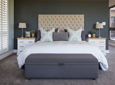 White bedside cabinets and button-tufted headboard in bedroom