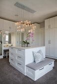 Chest of drawers, custom fitted wardrobes and integrated dressing table in elegant white dressing room