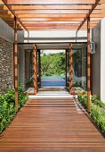 Wooden walkway below wooden pergola leading to entrance of modern house with view through to pool and trees