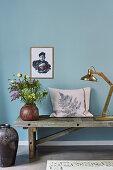 Mit Farnblatt bedrucktes Kissen auf einer alten Bank vor blauer Wand
