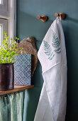 Mit Farnblättern bedrucktes Küchenhandtuch an grüner Wand