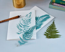 Fern leaves used as template for greetings card with natural motif