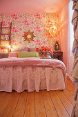 Bed with valance in romantic bedroom with floral wallpaper