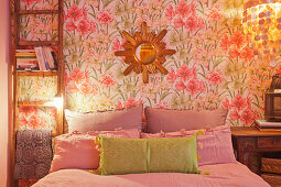 Ladder leant against floral wallpaper and used as bedside table in bedroom
