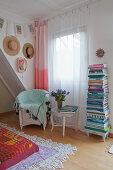 Vorhang mit Farbverlauf und bunter Bücherstapel am Fenster