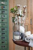 Baumwollzweige und Silberblatt in einer Vase mit Wollknäueln