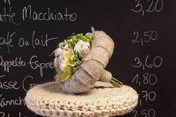 Winterlicher Blumenstrauß mit einer Manschette aus grauem Filz