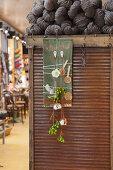 Grünes Brett mit Blumen an zwei Haken und mit Wollfäden umwickelt