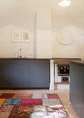 Minimalistische Küche mit grauen Fronten unter der Gewölbedecke