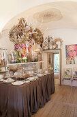 Üppig dekorierter Esstisch ohne Stühle unter der Gewölbedecke