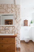 Old chest of drawers used as washstand against partition wall clad with stones