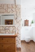 Waschbecken in alter Kommode an der Raumteilerwand mit Steinen
