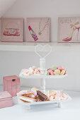 Pastellfarbene Süßigkeiten in einer Etagere vor mädchenhafter Deko