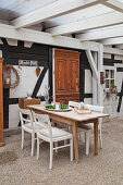Table and chairs on roofed terrace adjoining half-timbered house