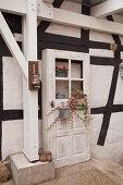 Alte Holztür mit Blumen als Deko am Fachwerkhaus