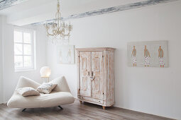 Modern armchair next to shabby-chic cabinet