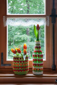 Preserving jar and beer bottle with crocheted covers on windowsill