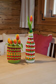 Preserving jar and beer bottle with crocheted covers on table