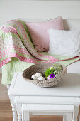 Dish on nest of side tables in front of white sofa with patchwork blanket