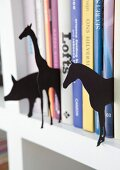 Various animal sihouettes made from black cardboard between books