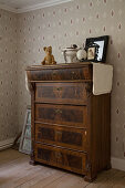 Battered, antique chest of drawers against vintage-style beige wallpaper