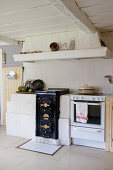 Cooker and old wood-fired stove below extractor hood in country-house kitchen