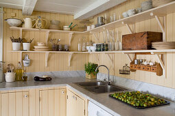 Shelves mounted on wall panelling painted yellow in country-house kitchen