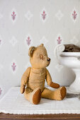 Old, patched teddy bear in front of vintage-style wallpaper