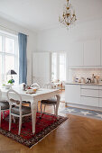 Classic dining table and medallion chairs on Oriental rug in front of kitchen counter