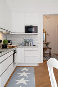 Simple kitchen counter and runner with star motif in open-plan interior