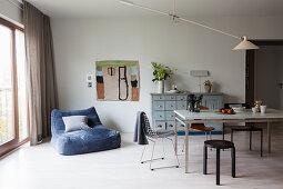 Blauer Samtsessel vor dem Esstisch mit verschiedenen Stühlen
